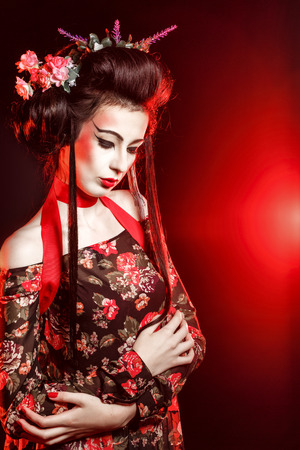 submissive: Submissive geisha. Girl with makeup and hair meekly bowed her head. The concept of traditional Japanese values.