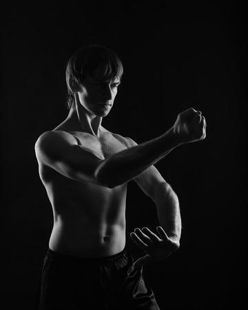 Kung Fu athlete shows kata kick and block. Low key. The concept of martial arts.