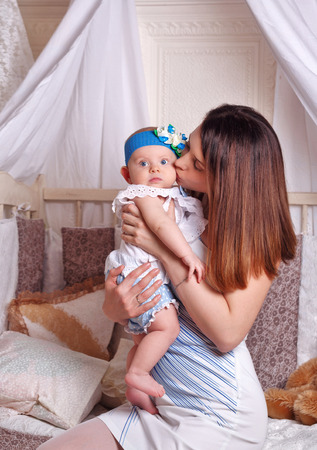parental love: A young mother holding a baby daughter in her arms and kisses her in the nursery. The concept of parental love.