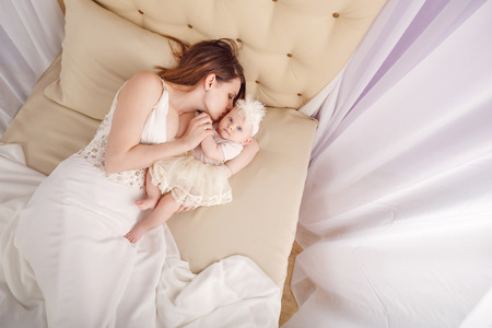 firstborn: Young mother kissing firstborn, lying on the couch in the nursery. The concept of happiness in the birth of children. Stock Photo