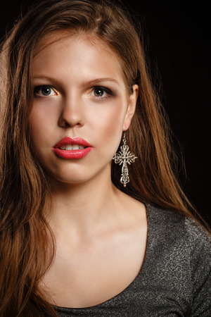 highfashion: Portrait of a teen girl with makeup and hairdo. High-fashion. Portrait on a black background. The girl looks into the camera. Stock Photo