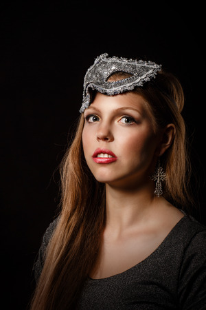 highfashion: Portrait of a teen girl with make-up and masquerade mask. High-fashion. Portrait on a black background.