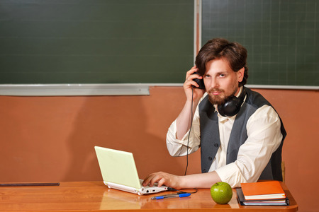 The teacher listens to music and talks in a video conference during a break between classes. Back to school.