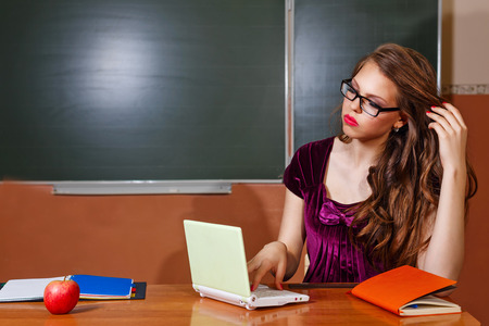 solves: Excellent pupil solves problems for your laptop. The concept of modern education. Back to school. Stock Photo