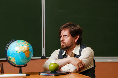 considers: Geography teacher carefully considers the globe. Back to school.