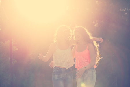 Best girlfriends hug. Girls dressed in the style of Pin-up girl. Hipster. Warm toning. Sunset. The concept of true friendship. Stock Photo