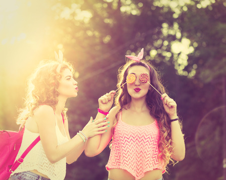 friends fun: Best girlfriends. Girl hides her eyes for lollipops. Girls dressed in the style of Pin-up girl. Hipster. Warm toning. Sunset. The concept of true friendship.