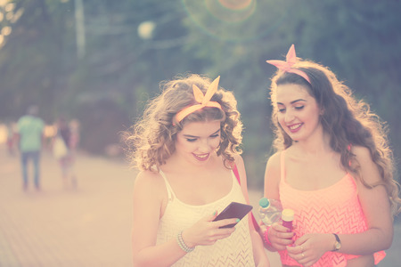 pinup girl: Best friends. Girls dressed in the style of Pin-up girl. girl looking photos on the phone. Hipster. Warm toning. The concept of true friendship.