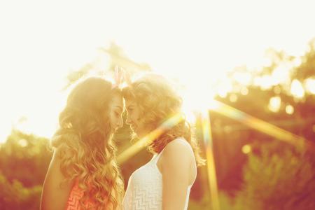 niñas sonriendo: Las mejores amigas están mirando a los ojos. Chicas vestidas al estilo de chica pin-up. Inconformista. tonificación caliente. La puesta del sol. El concepto de la verdadera amistad.