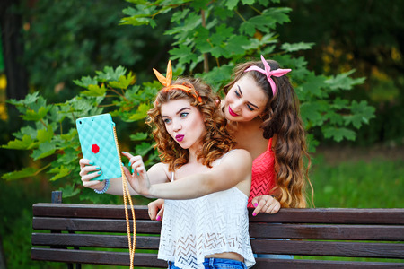 nice girl: Best girlfriends do funny photos to your phone. Group selfies. Girls dressed in the style of Pin-up girl. Hipster. Face duck. The concept of true friendship. Stock Photo