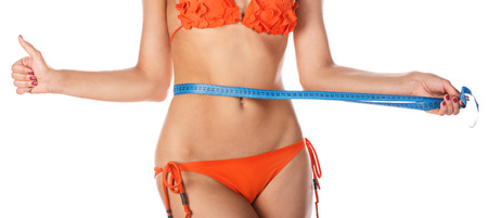 body care: Young slim woman measuring waist circumference and shows a thumbs up after a diet. Isolated on white background. The girl in swimsuit. The concept of excess weight loss and healthy eating. Stock Photo