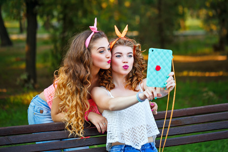 Best girlfriends are photographed on a bench in a summer park. Group selfies. Girls dressed in the style of Pin-up girl. Hipster. Face duck. The concept of true friendship.