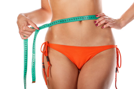 excess weight: Young slender woman measuring her waist after dieting and exercise sports. Isolated on white background. The girl in swimsuit. The concept of excess weight loss and healthy eating. Archivio Fotografico