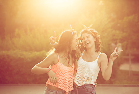 hugging: Best girlfriends hug. Girls dressed in the style of Pin-up girl. Hipster. Warm toning. Sunset. The concept of true friendship. Stock Photo