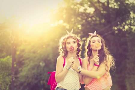 Best friends. The girls hide their lips for lollipops. Girls dressed in the style of Pin-up girl. Hipster. Warm toning. Sunset. The concept of true friendship. Stock Photo