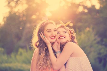 niñas sonriendo: Las mejores novias abrazar, retrato de primer plano. Niñas vestidas al estilo de pin-up girl. Hipster. Tonificación caliente. Sunset. El concepto de la verdadera amistad. Foto de archivo