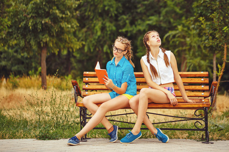 adolescente: Los mejores amigos están leyendo el diario sentado en un banco en un parque de verano. La muchacha adolescente vestido con pantalones cortos y una camisa. En las vacaciones de verano. El concepto de la verdadera amistad. Foto de archivo