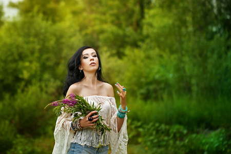 beautiful blonde woman: Young carefree boho girl holding a bouquet of wildflowers. Stylish lifestyle portrait. Girl in the woods.