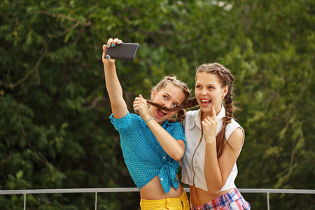 Best girlfriends teenagers being photographed in a summer park. Photo phone selfie. Girls dressed in shorts and a shirt. On summer vacation. The concept of true friendship. Foto de archivo