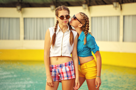 Teen girl in sunglasses standing near the fountain in summer park. Girls dressed in shorts and a shirt. On summer vacation. The concept of true friendship.