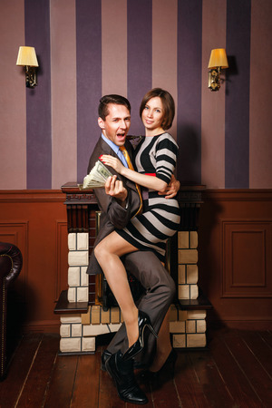 moneymaker: Business partners share the money. Man holding dollars and hugging a beautiful woman. Vintage interior. The concept of running a successful business.