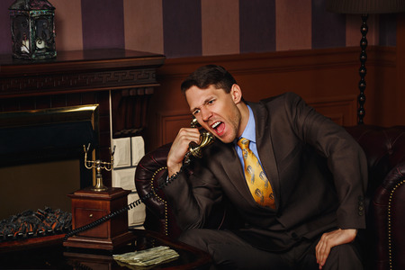 Businessman makes an important phone call. Man shouting into the phone. Vintage background. Leadership concept.