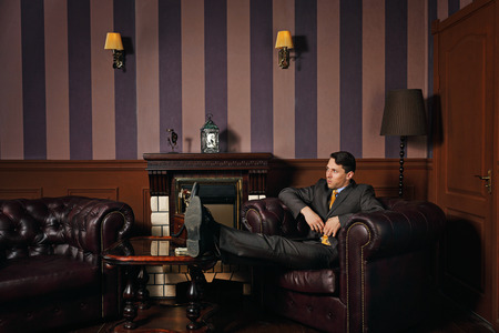 Successful businessman relaxing with his feet up on the coffee table, sitting in a leather armchair manager. Vintage background. Leadership concept.