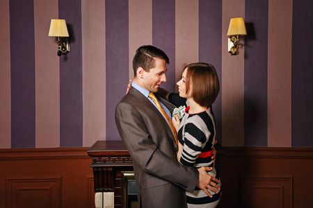 Businessman hugging his wife. The girl holds money in hand. Vintage interior. The concept of running a successful business. Stock Photo