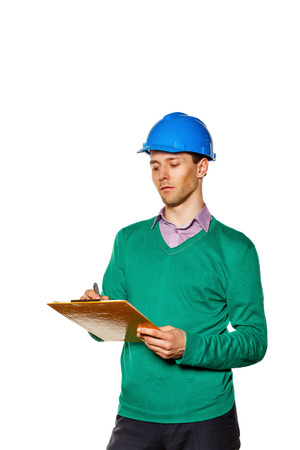 focuses: Young architect wearing a helmet. Construction worker making notes in the checklist. The man focuses on the job. The concept of modern construction.
