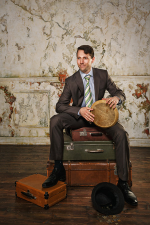bongos: Businessman sitting on suitcases. The man playing the bongos collecting money for a new project. A hat with coins lying at his feet. Business trip. Vintage background. The concept of a startup.