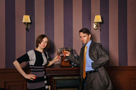 moneymaker: Business partners celebrate successful conclusion of the deal. Man and woman drinking sparkling wine. Vintage interior. The concept of running a successful business. Stock Photo