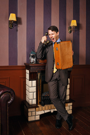 moneymaker: Successful businessman swearing by telephone. A man holding a suitcase. Business travel. Vintage background. Leadership concept.
