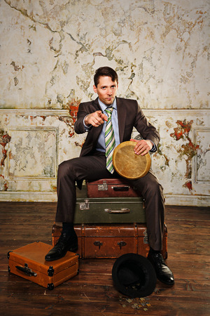 Businessman sitting on suitcases. The man playing the bongos collecting money for a new project. A hat with coins lying at his feet. Vintage background. The concept of a startup. Stock Photo