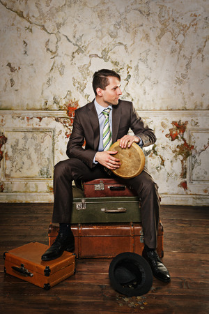 Businessman sitting on suitcases. The man playing the bongos collecting alms. A hat with coins lying at his feet. Business trip. Vintage background. The concept of a startup. Stock Photo