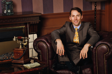 Successful businessman sitting in a leather executive chair. Coffee table with vintage telephone. Vintage background. Leadership concept.