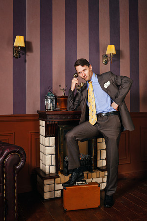 moneymaker: Successful businessman speaks by phone. The man put his foot on suitcase. Business travel. Vintage background. Leadership concept.