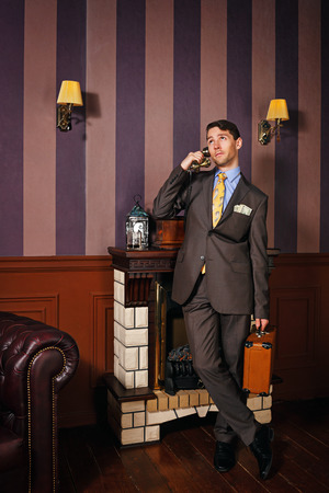 moneymaker: Successful businessman speaks by phone. A man holding a suitcase. Business travel. Vintage background. Leadership concept. Stock Photo