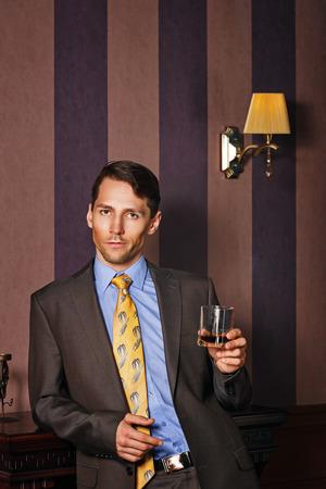 buen trato: Exitoso hombre de negocios con un vaso de whisky. Hombre celebra buen negocio. Fondo de la vendimia. Concepto de la dirección.
