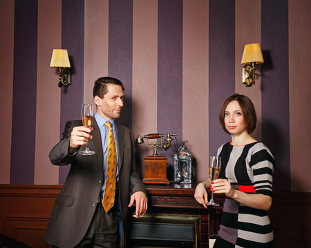 moneymaker: Business partners accept congratulations on the successful transaction. Man and woman drinking sparkling wine. Vintage interior. The concept of running a successful business.