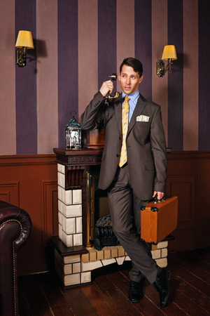 profit celebration: Successful businessman giving instructions over the phone. A man holding a suitcase. Business travel. Vintage background. Leadership concept.