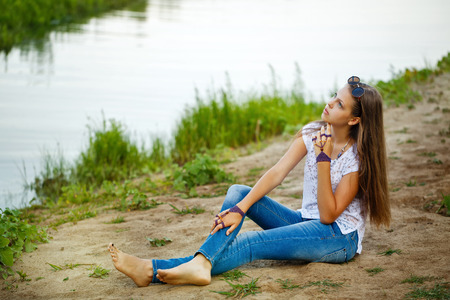 barefoot teens: Young carefree teenager girl sitting on the river bank. Stylish lifestyle portrait. Stock Photo