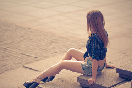 warm shirt: Seductive young girl in shirt and denim shorts sitting on the steps. Warm toning. The concept of youth fashion. Stock Photo