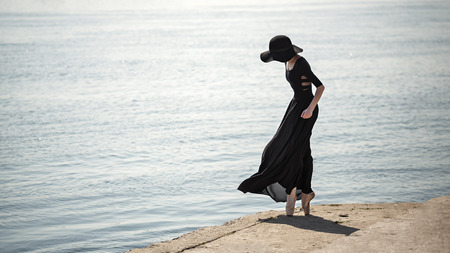 ballerina: Young slim ballerina in black dress and hat is dancing on the pier of the city. Summer day. The concept contemporary ballet. Performance on the street. Minimalism.