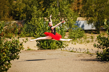 pas: Young slender ballerina in a red tutu dancing in the park. Summer day. The concept modern ballet. Performance on the street. Grande pas des chat