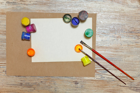 creative tools: Multicoloured gouache and paint brush lying on an empty sheet of paper. Tools of the artist and designer. The creative impulse. The concept of free artist.