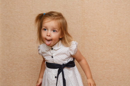 foxy girls: Little cute girl shows tongue. Positive emotions. The concept of carefree childhood.