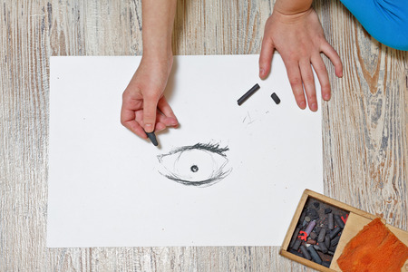 artists: The artist draws the eye with charcoal on paper. The concept of creativity.
