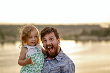 parentage: Bearded father holds on hands little daughter. The family walking. Background river and sunset. Concept of happy family relations. Stock Photo