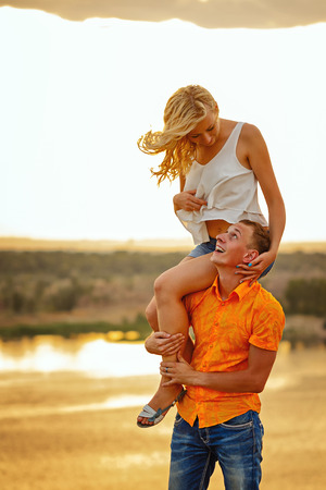 carrying girl: Loving couple on the river bank. Man carrying girl piggyback. Sunset. Summer day. The concept of a romantic relationship. Stock Photo