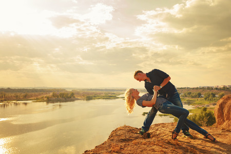 Loving couple on the river bank. Passionate dance. Summer day. The concept of a romantic relationship.